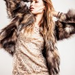 Portrait of attractive stylish woman in fur against grey background. — Foto Stock