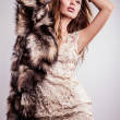 Portrait of attractive stylish woman in fur against grey background. — Stock Photo #18355053