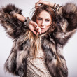 Portrait of attractive stylish woman in fur against grey background. — Stock Photo #18355373