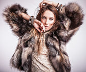 Portrait of attractive stylish woman in fur against grey background. — Stock Photo