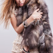Portrait of attractive stylish woman in fur against grey background. — Stock Photo #18703027