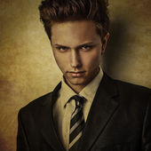 Elegant young handsome man in costume..Grunge style digital painted image portrait of men face. — Stock Photo