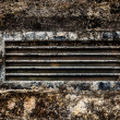 Old rusty dirty ventilation grid embedded in stone wall. - Stock Photo