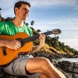 Attractive romantic guitarist play music siting on beach rock. — Stock Photo #23518193