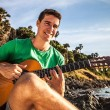 Attractive romantic guitarist play music siting on beach rock. — Foto de Stock