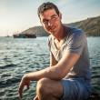 Relaxed attractive smiling man sit at evening near water.  — Stock Photo