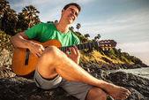 Atrakcyjny romantyczny gitarzysta grać muzyka lokalizacji na plaży rock. — Zdjęcie stockowe