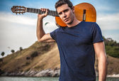 Handsome smiling man pose near evening beach with guitar. — Stock Photo