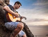 Attractive romantic guitarist play music siting on beach rock. — Stock Photo