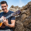 Handsome smiling guitarist play music siting on beach rock. — Stockfoto