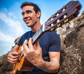 Handsome smiling guitarist play music siting on beach rock. — Stock Photo