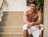 Relaxed handsome man poses sitting on stone steps. — Stock Photo