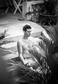 Adult attractive man relaxed on garden. Black-white photo. — Stock Photo