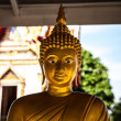 Golden buddha statue sitting cross legged at Temple - Stock Photo