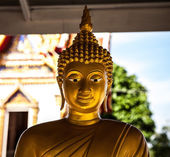 Golden buddha statue sitting cross legged at Temple — Stock Photo