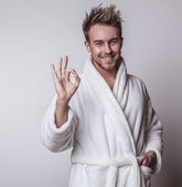 Handsome smiling young man in luxurious bathrobe. — Stock Photo