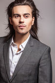 Elegant young handsome long-haired man in costume. Studio fashion portrait. — Stock Photo