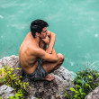 Young man on rocks next to the sea — Stock Photo