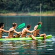 Strong young men in kayak - Stock Photo