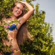Sexual beauty dressed bikini poses in an summer garden. — Stock Photo