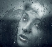 Art portrait of a beautiful young spooky woman, looks through grunge styled rainy window. — Stock Photo