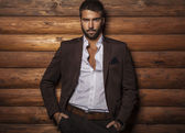 Portrait of young beautiful fashionable man against wooden wall. — Stok fotoğraf