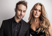 Portrait of young attractive couple posing at studio dressed in black fashionable clothes. — Foto de Stock