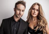 Portret van jonge aantrekkelijke paar poseren in studio gekleed in zwarte modieuze kleding. — Stockfoto