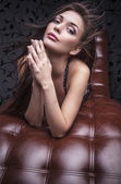 Young sensual & beauty woman posing on luxury leather sofa. — Stock Photo