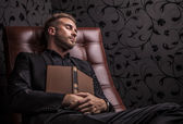 Handsome young business man in dark suit relaxing on luxury sofa. — Stock Photo