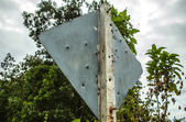 Road sign full of shotgun holes — Stock Photo