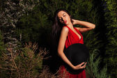 Beauty brunette women in red dress & hat pose at night park. — Stockfoto