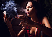 Attractive young women looking on mirror and smoke cigarette. — Stock Photo