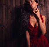 Lady in red pose on wooden background. Close-up photo. — Stock Photo