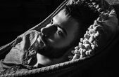 Portrait of young handsome serious man in a hammock. Black-white close-up photo. — Stock Photo