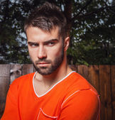 Portrait of young beautiful man in orange, against outdoor background. — Stock Photo