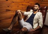 Красивый молодой человек в белом костюме, расслабляющий на роскошный диван. — Стоковое фото