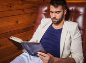 Handsome young man in white suit relaxing on luxury sofa with diary. — Foto Stock
