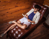 Handsome young man in white suit relaxing on luxury sofa with diary. — Foto de Stock