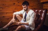 Bel giovane uomo in tuta bianca rilassante sul divano di lusso con diario. — Foto Stock