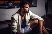 Young attractive bearded men in white suit pose in modern room. — Stock Photo