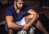 Young attractive bearded men pose in modern room. Close-up photo. — Photo