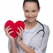 Smiling doctor holding a red heart — Stock Photo #39274857