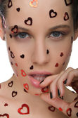 Young beautiful woman with heart on face — Stock Photo