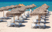 Beautiful beach with deck chairs and umbrellas — Stock Photo