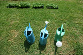 Three plastic watering cans — Stock Photo