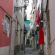 Cobblestone Alfama street with laundry hanging - Stockfoto