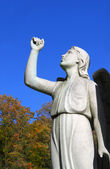 Angel statue in cemetary with raised arm — Stock Photo
