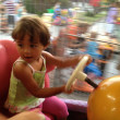 Stock Photo: Blurred movements of Baby enjoying merry go round