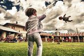 Baby kasta en docka i luften på en utomhus park — Stockfoto
